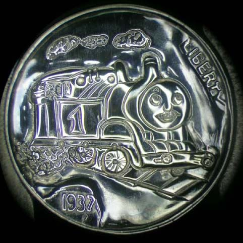 Hobo Nickel Engraved With Thomas The Train. Thomas Has A Smiling Face, Is Belching Smoke, And Rolling Along On Railroad Tracks.